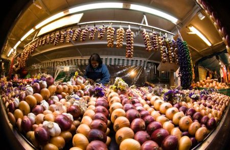 "A vendor sells strings of onions at her stall at the annual ""Zibelemaerit"" onion market in Bern November 23, 2009. Farmers sell more than 50 tonnes (50,000 kg) of onions and garlic during the traditional one-day autumn market in Bern's city centre on the fourth Monday of November. Picture taken with a fish-eye lens. REUTERS/Michael Buholzer (SWITZERLAND SOCIETY BUSINESS IMAGES OF THE DAY)"